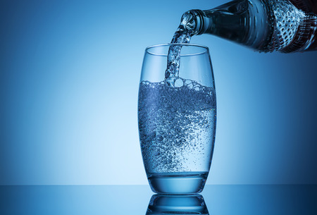 bottleneck: glass with pouring mineral drink water Stock Photo