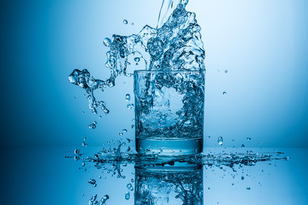 glass with splashing drink water Stock Photo