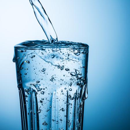 Glas gießt Wasser ist überfüllt