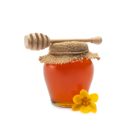 blossom honey: glass of bio honey with wooden honey dipper isolated on white background