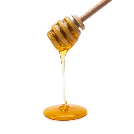 houten honing dipper met gouden honing op wit