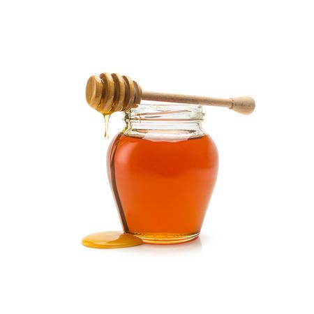 Glas Naturhonig und Honiglöffel auf weiß isoliert Lizenzfreie Bilder