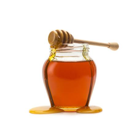 Überlaufen Glas Honig mit Honiglöffel isoliert auf weißem Hintergrund