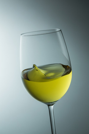 white wine glass: glass of fresh white wine from the winery is swinging with wave Stock Photo