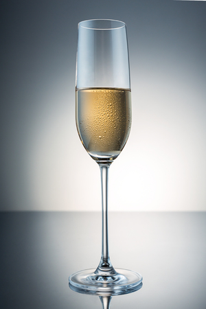condensation: glass of champagne with drops of condensation on black gradient background