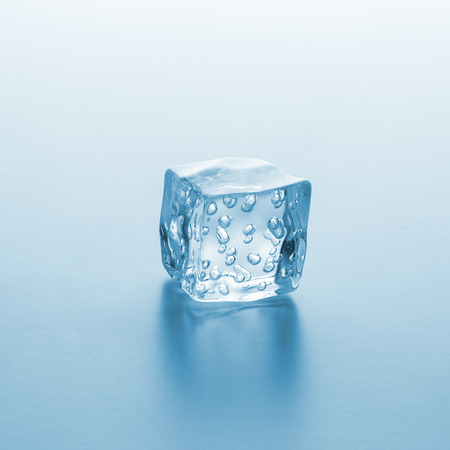 cube of ice with oxygen bubbels on blue gradient background