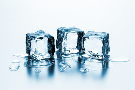 melting ice: group of three melting ice cubes with drops of water Stock Photo