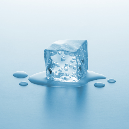melting ice: cube of melting ice with oxygen bubbels and drops of water