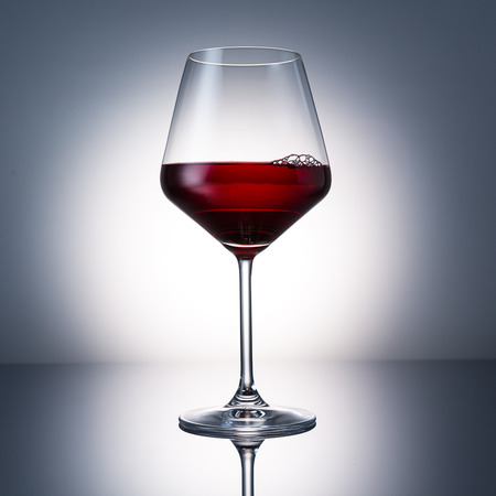 investigated: glass of red wine with bubbels on black gradient background