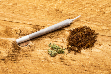 intoxicant: joint with cannabis and tobacco heap on wood