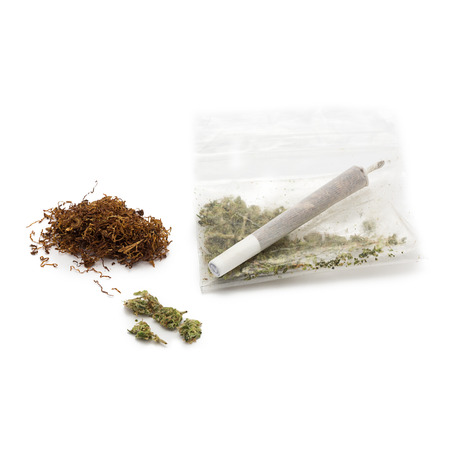 intoxicant: heap of tobacco with a plastic bag of marijuana and joint on white Stock Photo