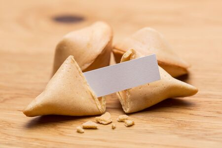 fortunately: A group of fortune cookies with message note on wooden table