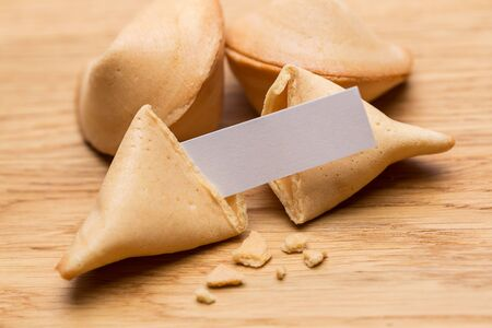 fortunately: A open fortune cookie with note on wooden background