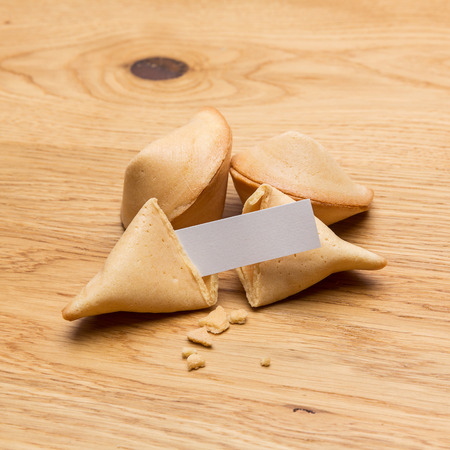 fortunately: A open fortune cookie with note and crumbs on wooden background Stock Photo