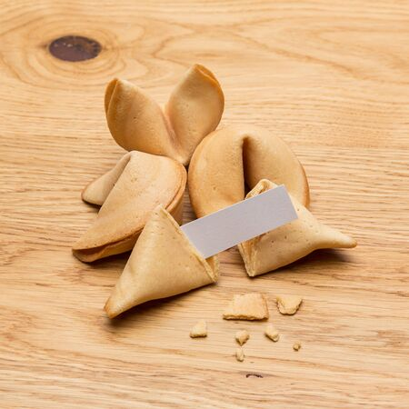 fortunately: A group of fortune cookies with a message note on wooden table background Stock Photo