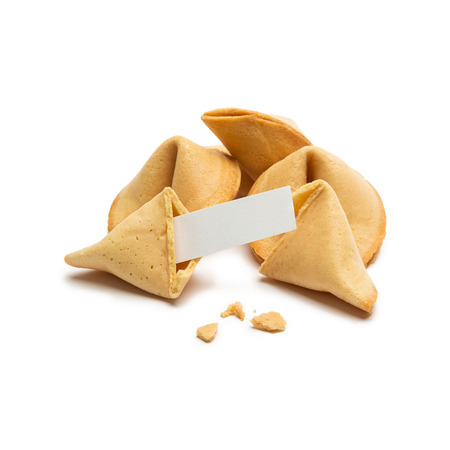 A chunk fortune cookie with note and crumbs on white background Foto de archivo