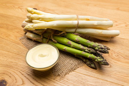 bundles: Two bundles of Asparagus spears with hollandaise sauce varieties on wooden background