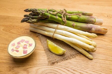 bundles: A mix of green and white asparagus with hollandaise sauce and lemon bundles on wooden background