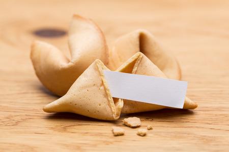 galletas: Una galleta de la fortuna trozo con la nota en el fondo mesa de madera