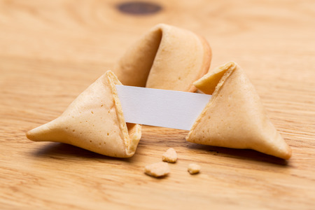 fortunately: A open fortune cookie with note on wooden table background Stock Photo