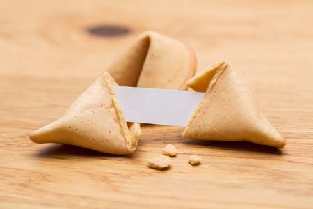A open fortune cookie with crumbs and note on wooden table background