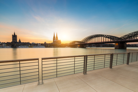 europe: cologne city with cathedral and Hohenzollern from the Rhine Boulevard at sunset