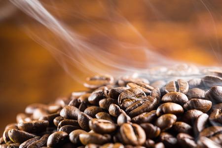 stapel van hete koffie bonen met rook Stockfoto