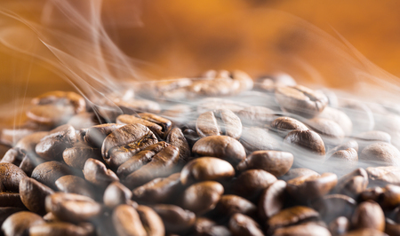 Heap of brown hot coffee beans with smoke