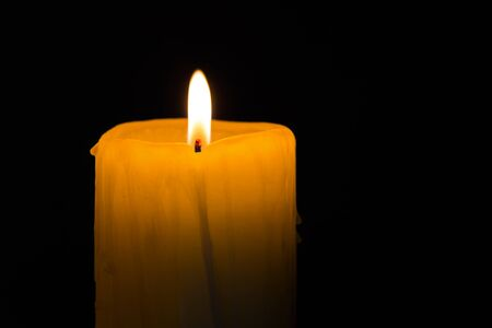 esotericism: yellow candle light on dark background