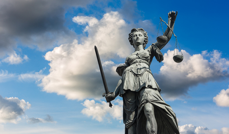 parole: Justitia (Lady Justice) sculpture with cloudy sky in Frankfurt, built in 1887