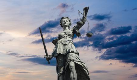 justicia: estatua lady Justitia con el cielo nublado atardecer