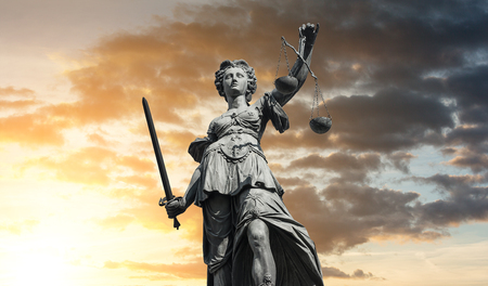 Statue of Lady Justice (Justitia) with sunset sky