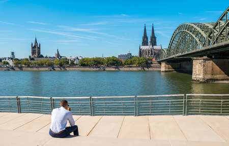 young businessman spending his time at the Deutzer rhine boulevard in Cologne at summer