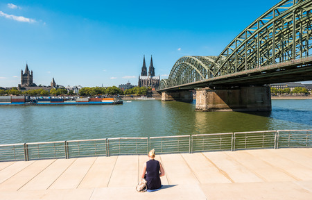 career fair: single woman pending the time at the Deutzer rhine boulevard at a summer day in Cologne Stock Photo