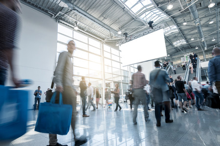 wazig mensen lopen in een moderne hal van een European Trade Fair Stockfoto