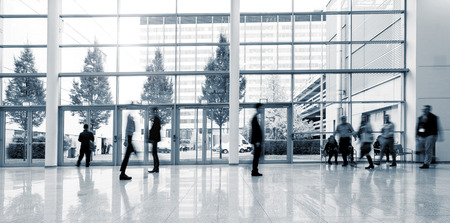 group of Blurred people walking in a business center lobby