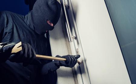 Inbreker het dragen van zwarte kleren en breken in een huis in de nacht
