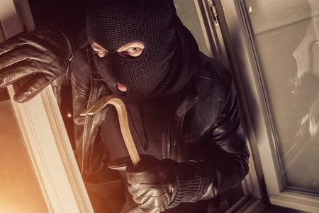 crowbar: Burglar using crowbar to break into a house at night Stock Photo