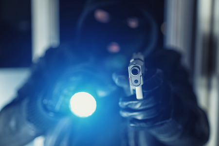Burglar or a thief holding a gun with flashlight in a house