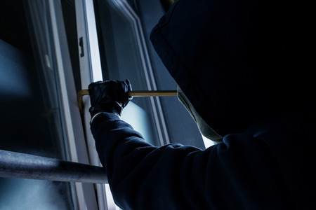 burglar using crowbar to break into a victims house window