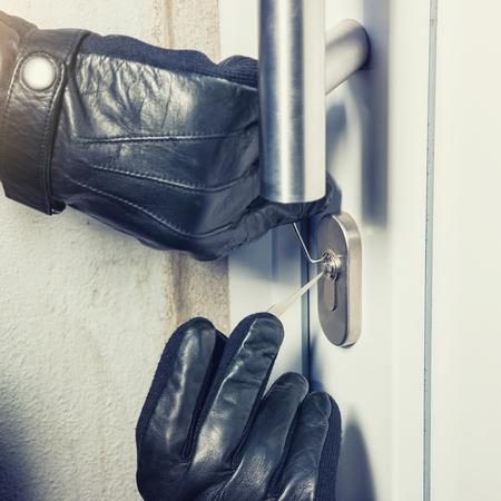 burglar holding lock picker to open a door