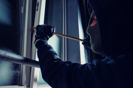 crowbar: burglar using crowbar to break into a victims house at night Stock Photo