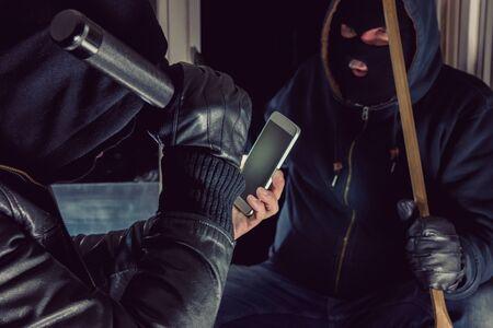 Two burglar use smartphone for a Housebreak