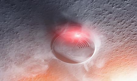 smoke detector with white smoke and red warning light Foto de archivo