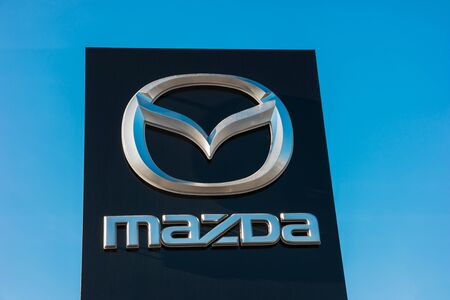 manufacturer: AACHEN, GERMANY JANUARY, 2017: Mazda dealership sign against blue sky. Mazda is a Japanese car maker and Produces over 1 million vehicles per year. Editorial