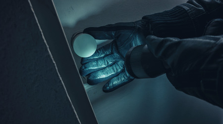 burglar with leather gloves and torch opens a victim's door at Night Stok Fotoğraf