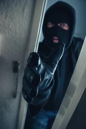 masked burglar entering a victim's home door