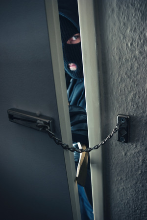 masked burglar use crowbar to breaking into a home door with chain