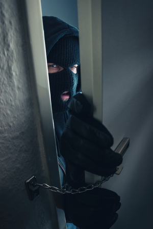 dangerous masked burglar breaking into a victim's home door