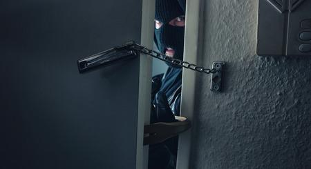 dangerous masked burglar with crowbar breaking into a victim's home door Stok Fotoğraf